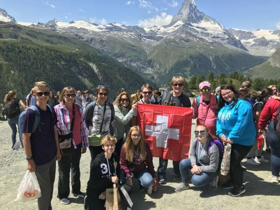 Members of the Manistee High School Band who took part in the Michigan Ambassadors of Europe trip that went to London, Paris, Switzerland, Liechtenstein, Austria and Germany pose is front of some of the beautiful scenery they saw on the trip.