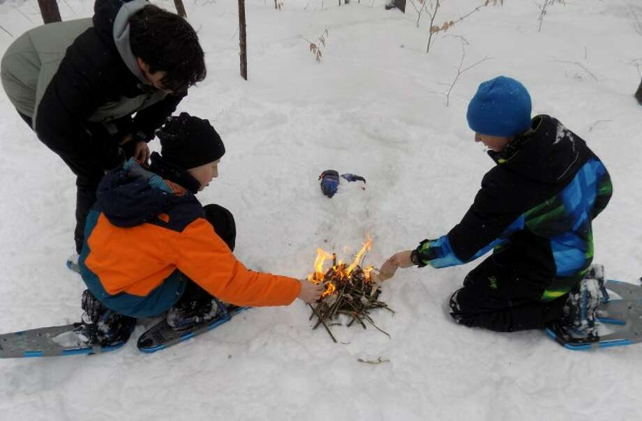 Manistee Catholic Central students Sam Madsen, Blake Johnson and Ian Kamaloski learn the skills of fire building at the Au Sable Trails Environmental Institute.