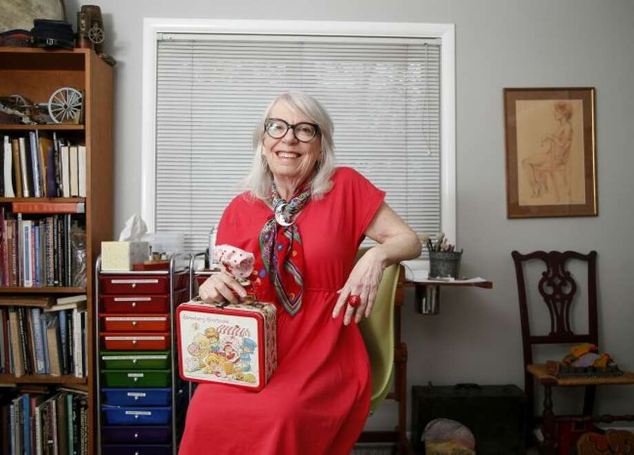 Muriel Fahrion, the creator of the Strawberry Shortake cartoon franchise, sits with a selection of memorabilia at her home studio in Tulsa, Okla., on Monday, March 25, 2019. (Matt Barnard/Tulsa World via AP)