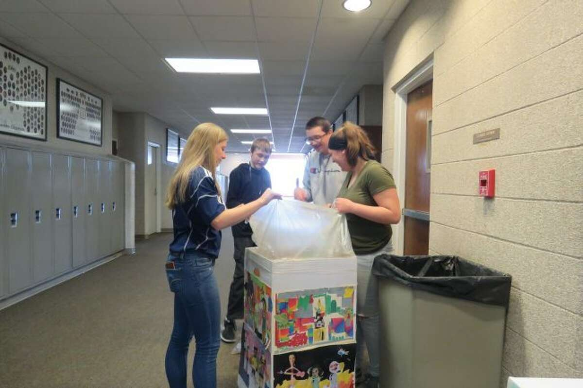 Manistee National Honor Society members prepare the recycling bins they put up at 10 location in the Manistee Middle/High School building. The students ares testing a recycling program for cans and bottles in the school.