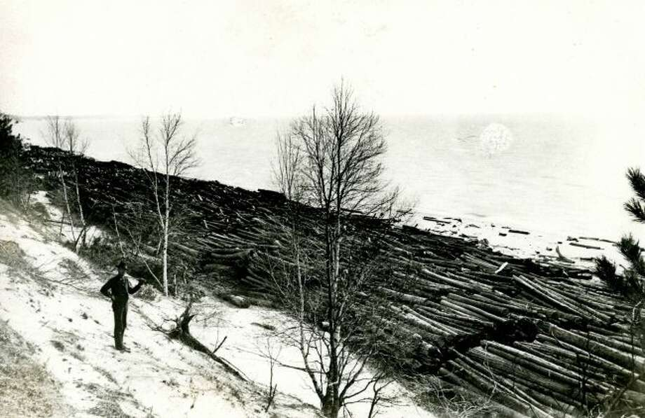 A rollway in Manistee County where logs are rolled down the hill to the Manistee River is shown in this late 1800s photograph.