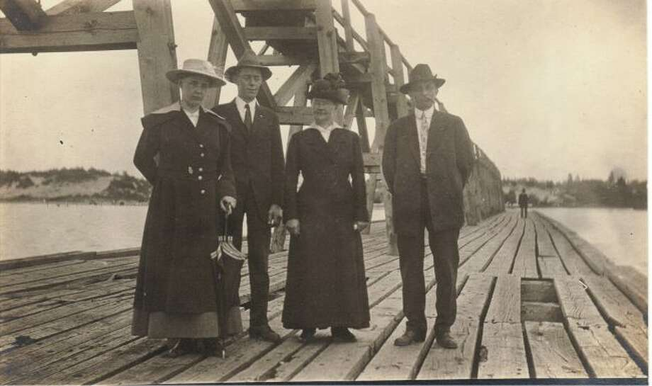 A group of Manistee citizens enjoy a day walking on the pier at Fifth Avenue Beach in the early 1900s.