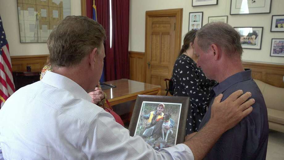 Dean Palozej, of Stafford, shows Gov. Ned Lamont a photo of his son who died of a fentanyl overdose. Palozej attended a ceremonial signing of a bill that raised the penalty for selling illicit fentanyl. Photo: Steve Hamm / C-Hit.org