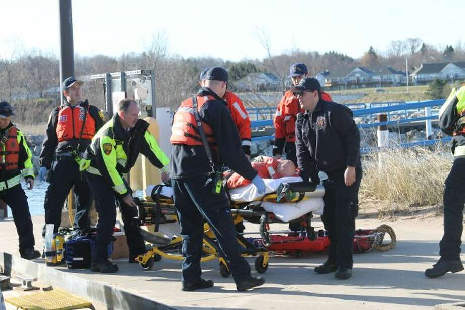 "Crew members unload the ""patient"" from the boat, an then transport him to the ambulance. (Ashlyn Korienek/News Advocate)"
