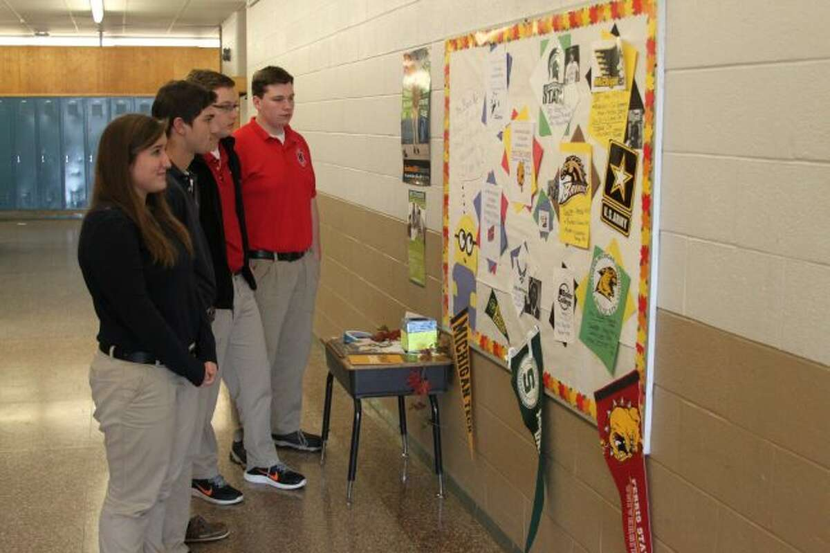 One of the many things that students in Manistee County do during college application week is decorate the school with things about the various colleges and universities. Shown from a past College Application Week event are students from Manistee Catholic Central looking at a bulletin board full of information on colleges.