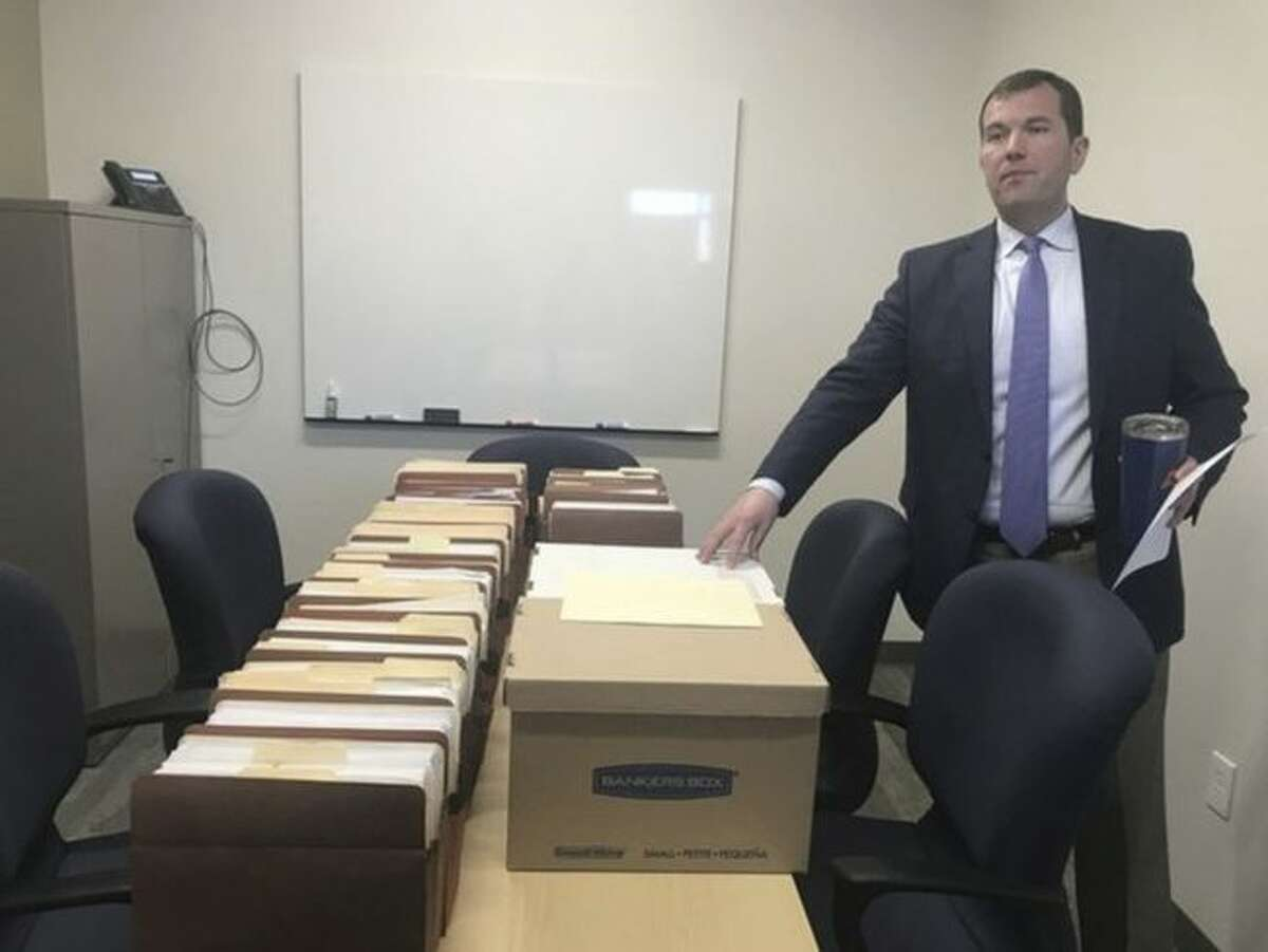 Marijuana Regulatory Agency Executive Director Andrew Brisbo displays files associated with one of the applications for medical marijuana licensing in Michigan at the bureau's office in Lansing, Mich. on May 1, 2018. (Lauren Gibbons/Ann Arbor News via AP)