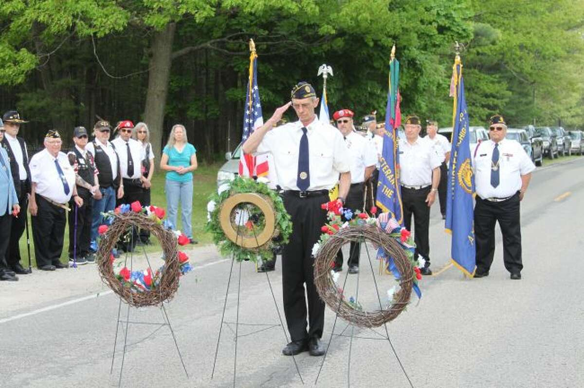 A member of the American Legion Post No. 10 salutes after placing a poppy on the wreaths at the Memorial Day ceremony on Merkey Road.