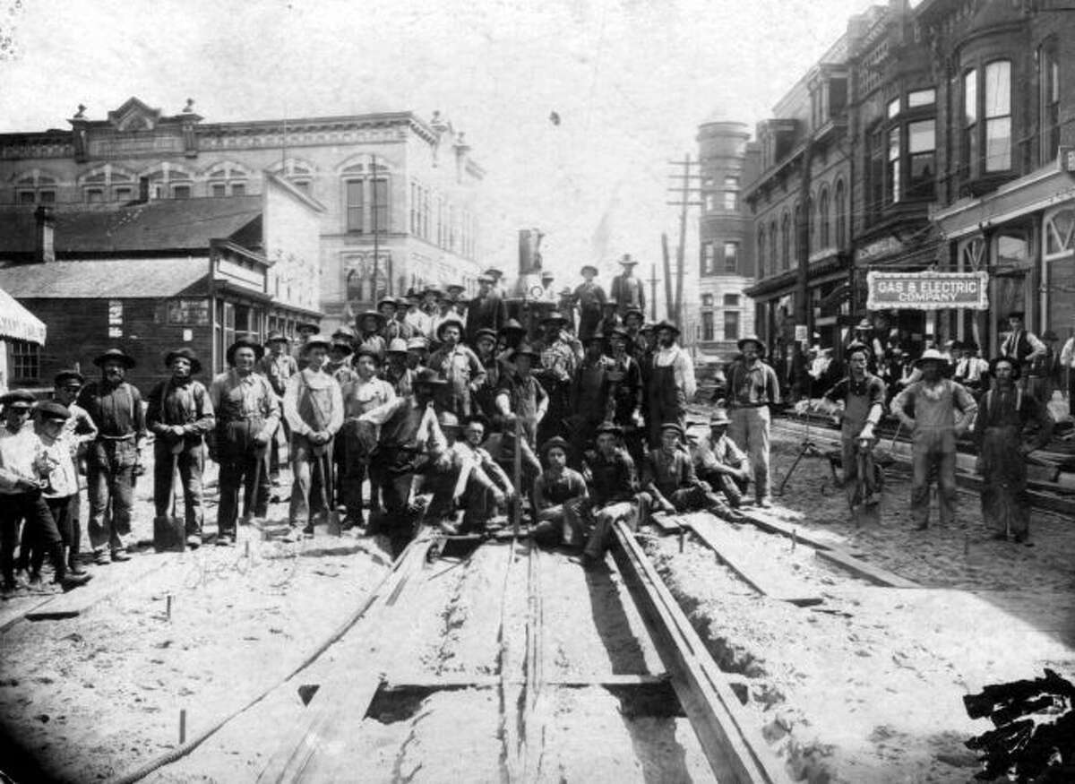 Workers constructing a new street in downtown Manistee gather together in this early 1900 photograph.
