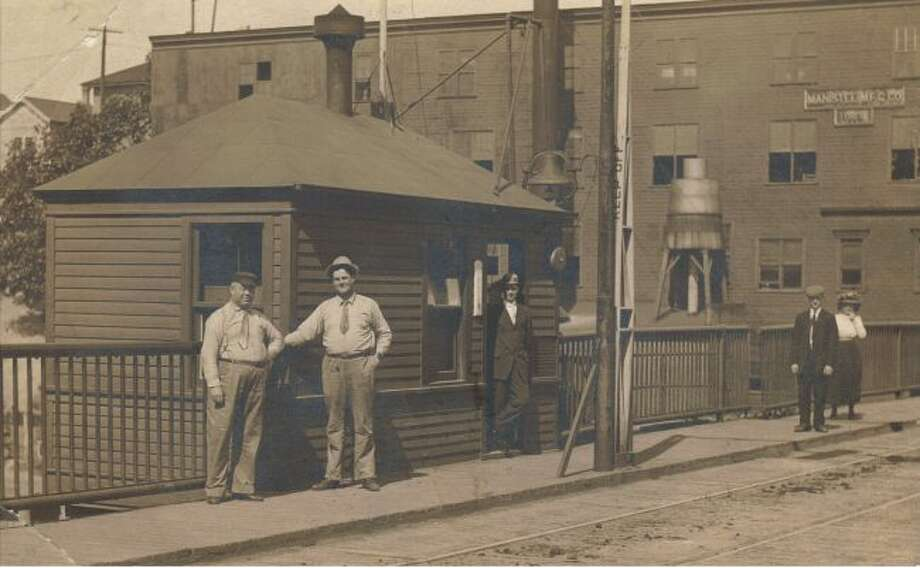 This photograph shows the Maple Street Bridge in the early 1900s with several residents at the bridge tender's building.