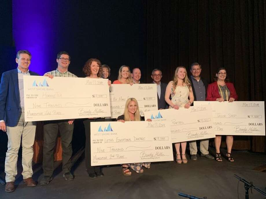 All 2019 Momentum Business Plan Competition contestants on stage with checks and judges (left to right) aer Tom Paine, Metalworks Inc.; Chris Turnbull and Carmen Biggs, HumaniTea; Kathy Maclean, Spindrift Cyclesports; Mary Case, Art by Mary Case; Ray Biggs, West Shore Bank; Jim Scatena, management consultant; Sarah Stechschulte, Inspired Parties; John Wilson, Western Land Services/Pennies from Heaven Foundation; Tracy Sheid, The Tailor Shop; and Leta Bowman, Leta's Educational Daycare (front row). (Courtesy photo)