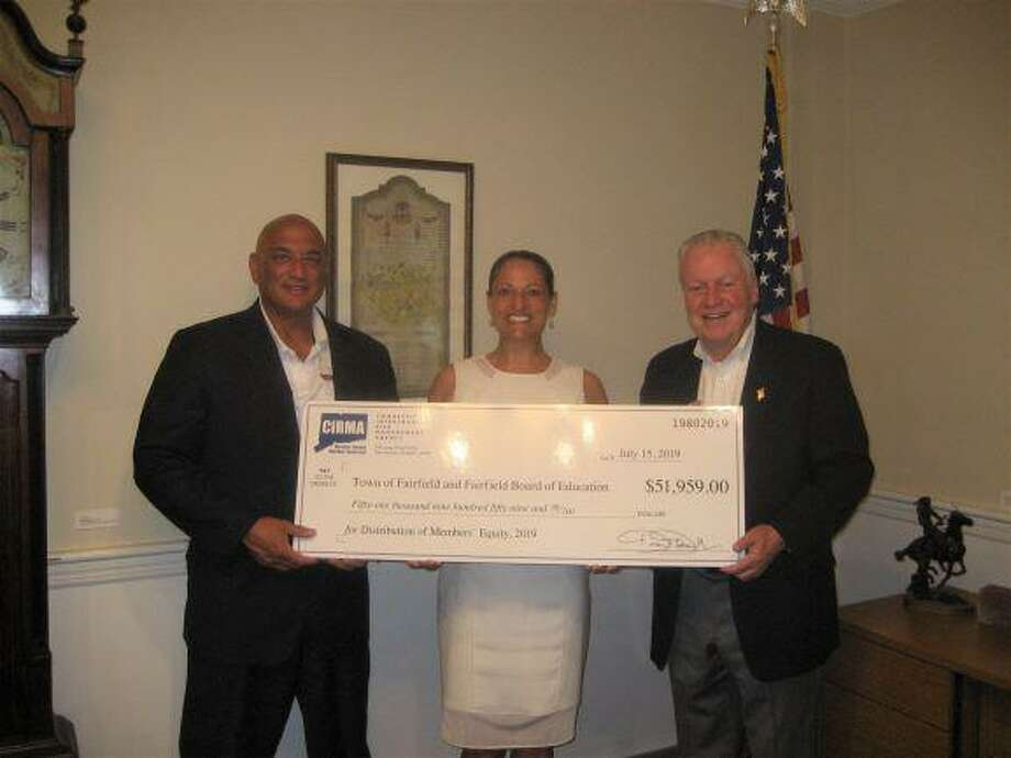 Fairfield's Human Resources Director Emmet Hibson, CIRMA's Senior Underwriter Ashley L. Reda and First Selectman Mike Tetreau at a check presentation ceremony in Independence Hall. Photo: Contributed Photo