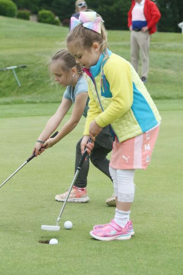 Sylvie Thompson, 6, sinks a putt Friday during the junior golf clinic at Manistee National. (Dylan Savela/News Advocate)