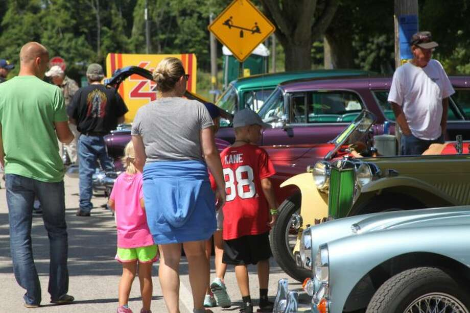 A family walks through the car show at Arcadia Days in 2018. (News Advocate File Photo)