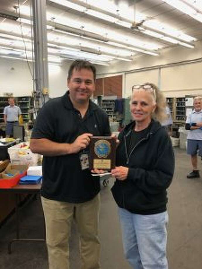 Mail carrier Francine Bretschneider is awarded for safely driving 1 million miles with the U.S. Postal Service. Manistee postmaster, Todd Blank presents her plaque. (Contributed by Rose Deneke)