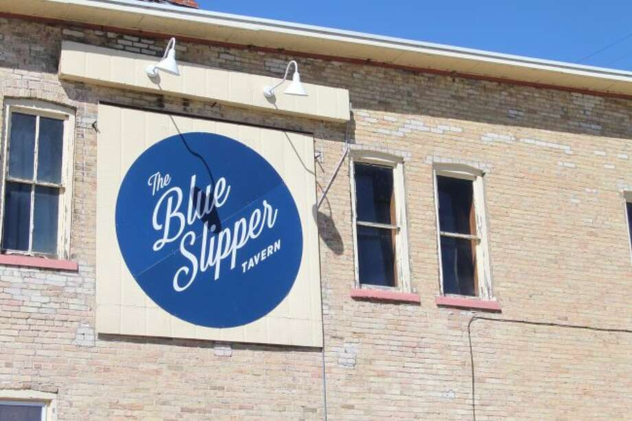 People passing by this sign on M-22 often stop in to find out what's in store at the Blue Slipper Tavern.