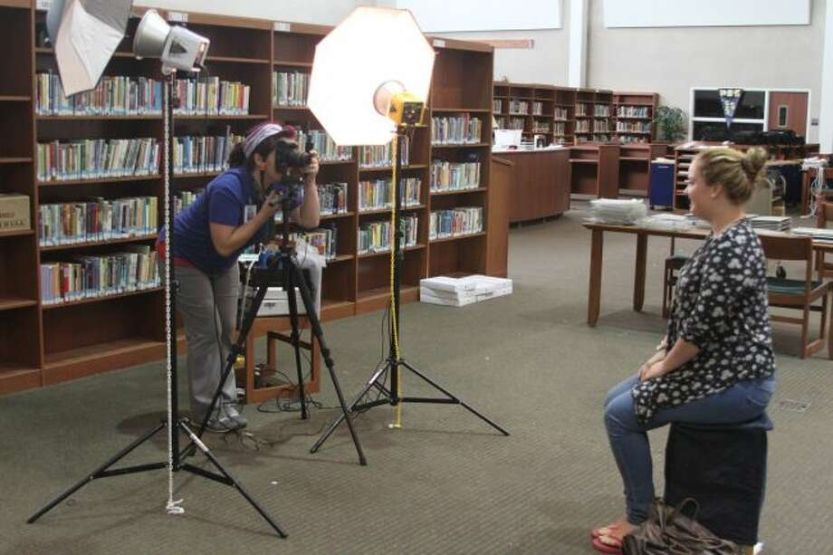 Hillary Rees of GPI Photography poses Manistee High School student Emma Peterson for her calls picture on Monday morning.