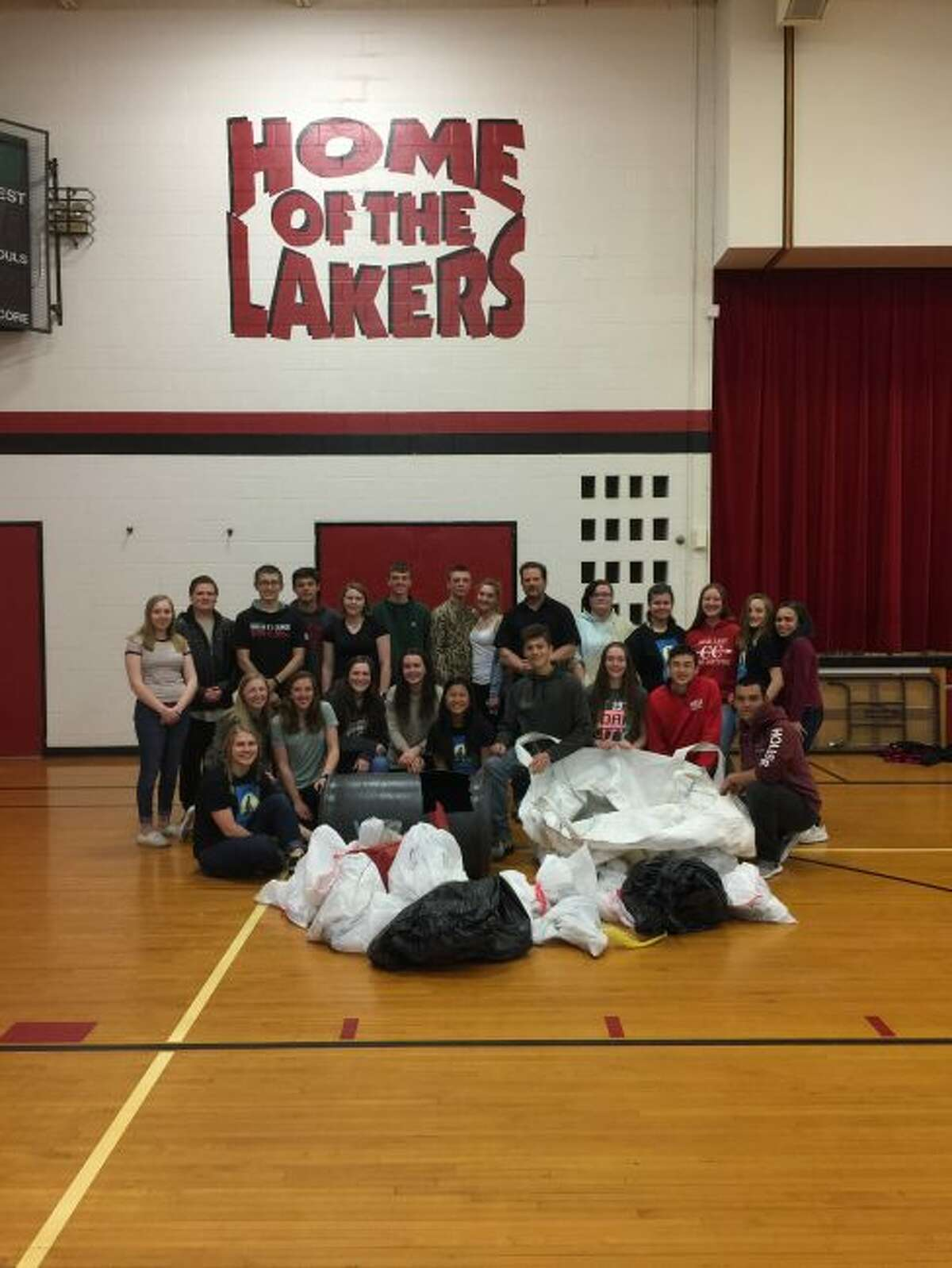 Bear Lake School students along with teacher John Prokes show their community pride as they display the bags of plastic trash they collected off the shore of Lake Michigan by the Sleeping Bear Dunes National Park.