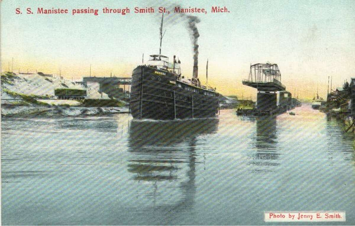 This Jenny Smith photograph shows the steamer S.S. Manistee churning past the Smith Street Bridge in Manistee on its way to its port in the Great Lakes.