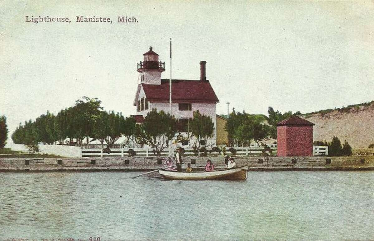 A fishing boat sails in front of the Manistee Lifesaving Station in this early 1900s photograph.