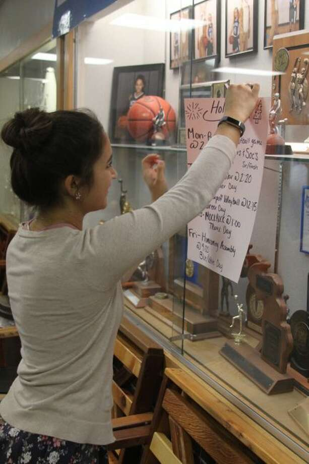 Brethren High School student Eleni Guenther puts up a poster with the activities for the Brethren High School Homecoming. This week students will be participating in a variety of events leading up to their game on Friday against Mesick.
