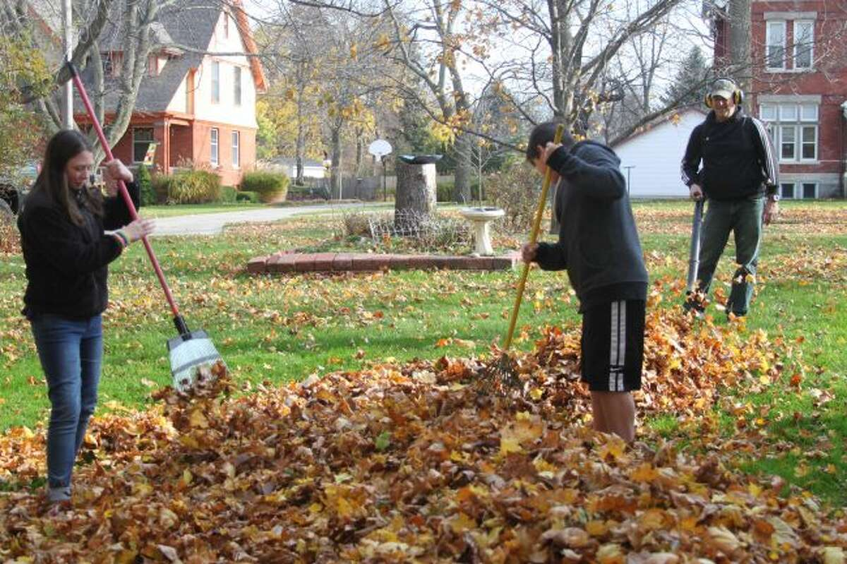 Greg Hornkohl blows leaves into a pile where his children Adam and Claire rake them together on Friday morning at Greg's parents house on Cedar Street. Manistee residents were out taking advantage of the unseasonably warm temperatures to get the last of their fall chores done for the season.
