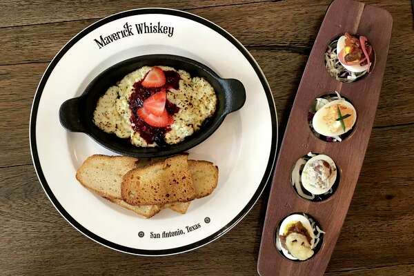 Goat cheese and strawberries served in a cast-iron dish and a flight of deviled eggs from Maverick Whiskey