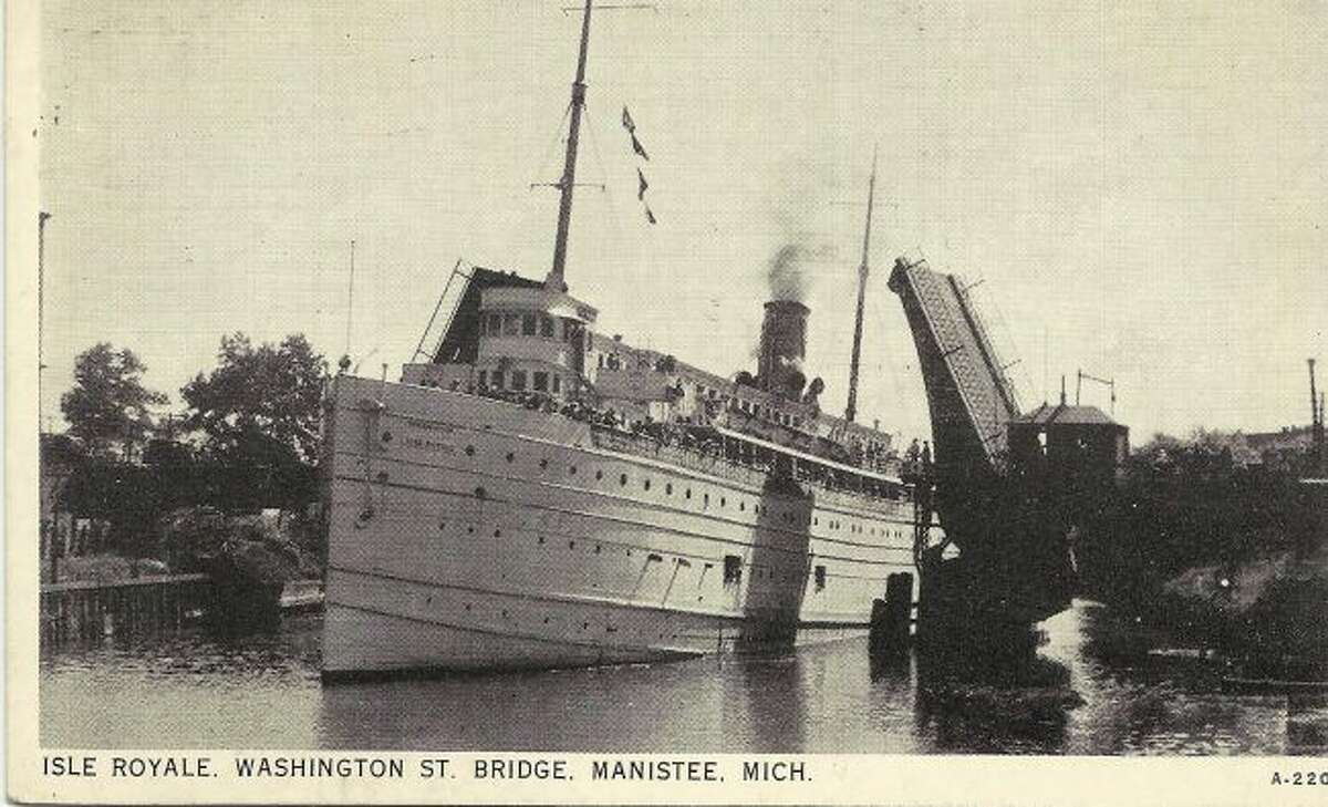 The steamer Isle Royale is shown passing down the Manistee River Channel with a load of passengers in the early 1900s.