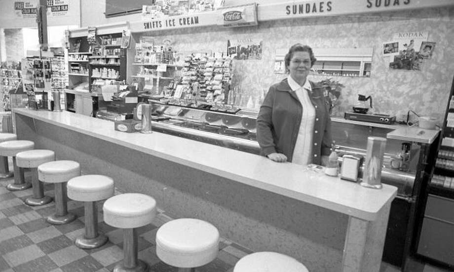 Charlotte Franckowiak stands behind the counter the last drug store soda fountain in Manistee in February, 1981. The soda fountain, formerly located at 359 River St., ceased operation when Saylor's Rexall Pharmacy closed.