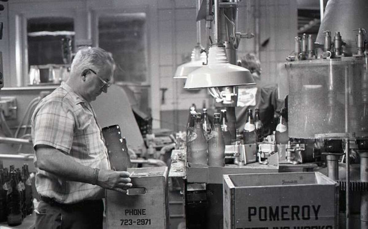 Along with the article published in the News Advocate, came several photographs of the bottling factory including this one of John Pomeroy packaging bottles of Squirt into a crate.