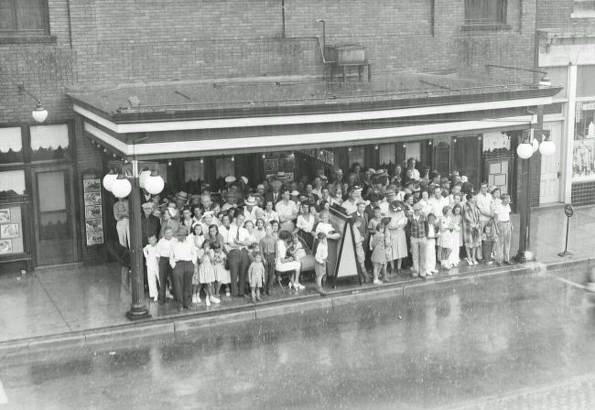 A group gathers under the canopy of the Lyric Theater during the Forest Festival Parade of 1940.