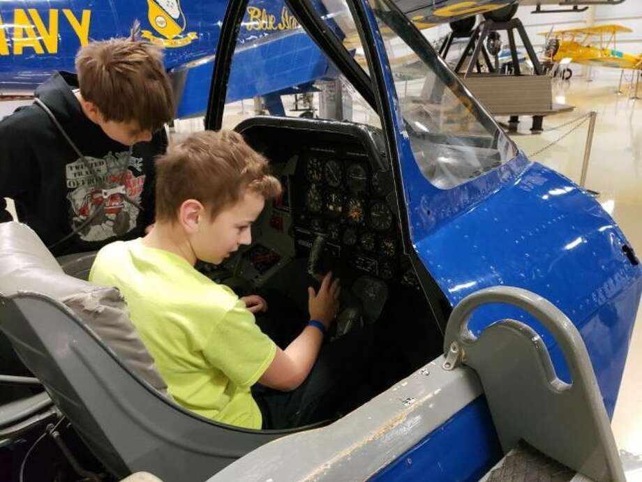 Onekama Consolidated School seventh grade student Landon Tennant checks out the inside of an airplane while eighth grade student Jacob Evans looks on.