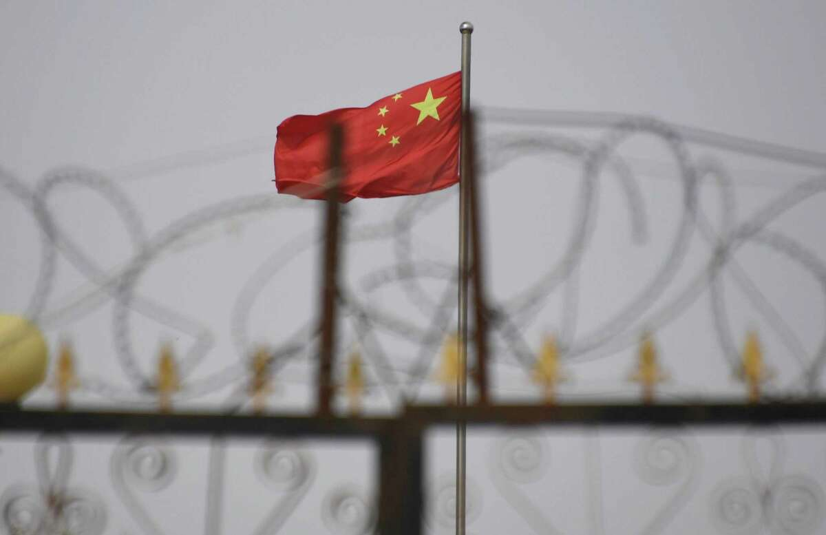The Chinese flag behind razor wire at a housing compound in Yangisar, south of Kashgar, in China's western Xinjiang region. - A recurrence of the Urumqi riots which left nearly 200 people dead a decade ago is hard to imagine in today's Xinjiang, a Chinese region whose Uighur minority is straitjacketed by surveillance and mass detentions. A pervasive security apparatus has subdued the ethnic unrest that has long plagued the region.