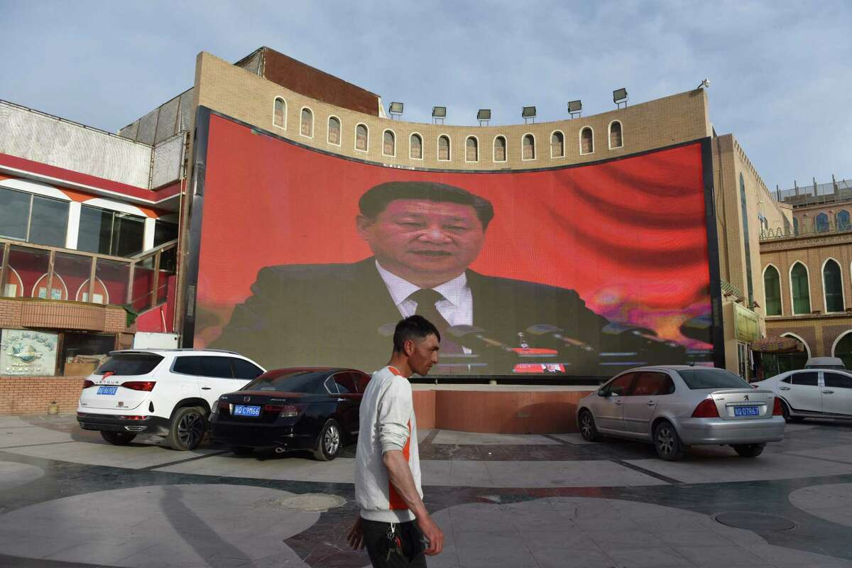 """A man walking past a screen showing images of China's President Xi Jinping in Kashgar in China's northwest Xinjiang region. - China has enforced a massive security crackdown in Xinjiang, where more than one million ethnic Uighurs and other mostly Muslim minorities are believed to be held in a network of internment camps that Beijing describes as """"vocational education centres"""" aimed at steering people away from religious extremism."""