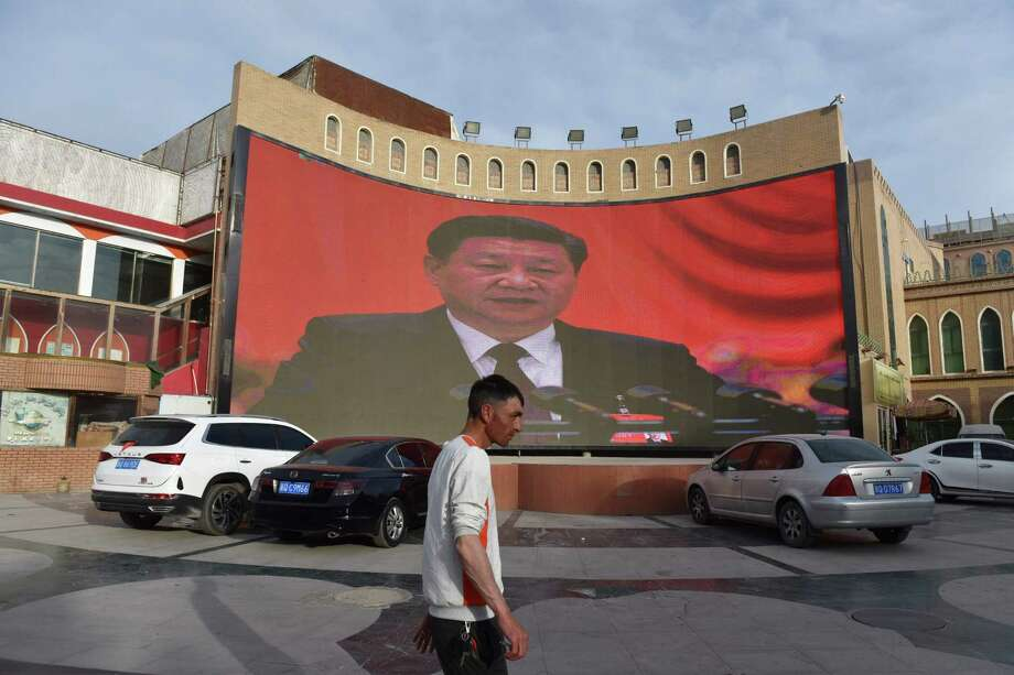 "A man walking past a screen showing images of China's President Xi Jinping in Kashgar in China's northwest Xinjiang region. - China has enforced a massive security crackdown in Xinjiang, where more than one million ethnic Uighurs and other mostly Muslim minorities are believed to be held in a network of internment camps that Beijing describes as ""vocational education centres"" aimed at steering people away from religious extremism. Photo: GREG BAKER, Contributor / AFP/Getty Images / AFP or licensors"