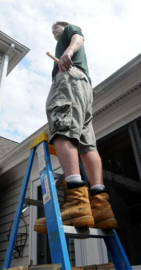 Jason Pease, owner of Fairfield County Paintworks, demonstrates that you should never go higher on a step ladder than two rungs from the top. Thursday July 29, 2010 in Newtown. Photo: Lisa Weir / The News-Times Freelance