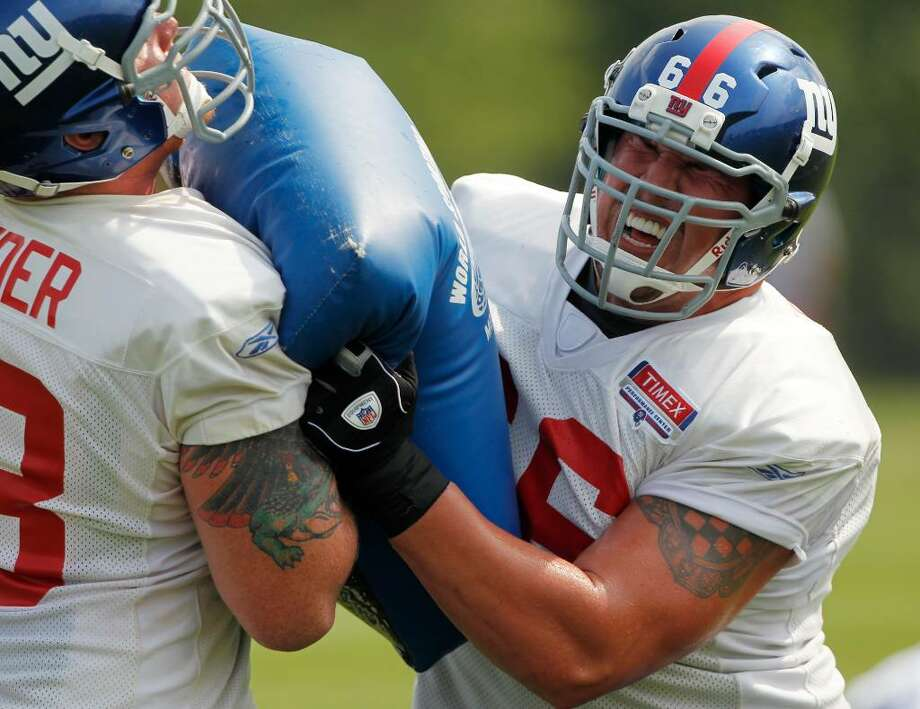 New York Giants offensive lineman David Diehl (66) performs a drill with teammate Jacob Bender during NFL football training camp in Albany, N.Y., on Monday, Aug. 2, 2010. (AP Photo/Mike Groll) Photo: AP