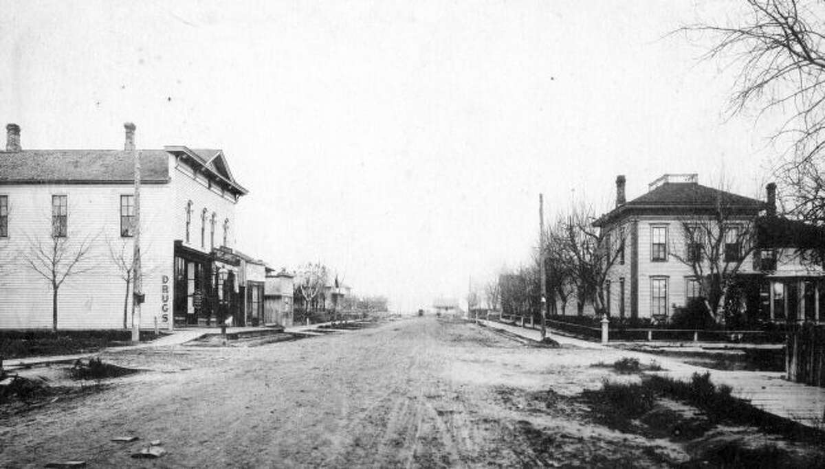 A view of the unpaved streets and board sidewalks looking east on Sibben Street circa 1890s. The street bond issue that was passed by Manistee citizens in 1902 would allow several city streets to finally be paved.