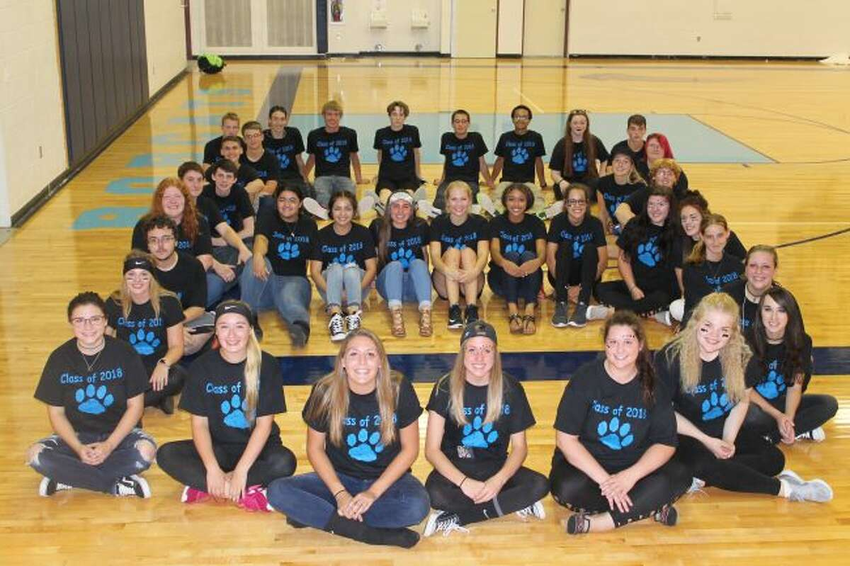 """Members of the senior class sporting T-shirts with Bobcat paws on them form the letter """"B"""" on color day."""