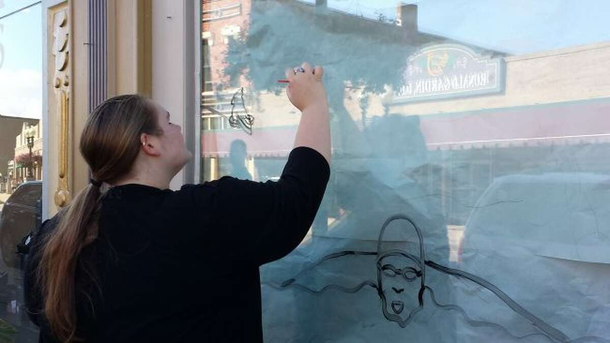 Manistee High School students painted windows in downtown Manistee in preparation for Homecoming.