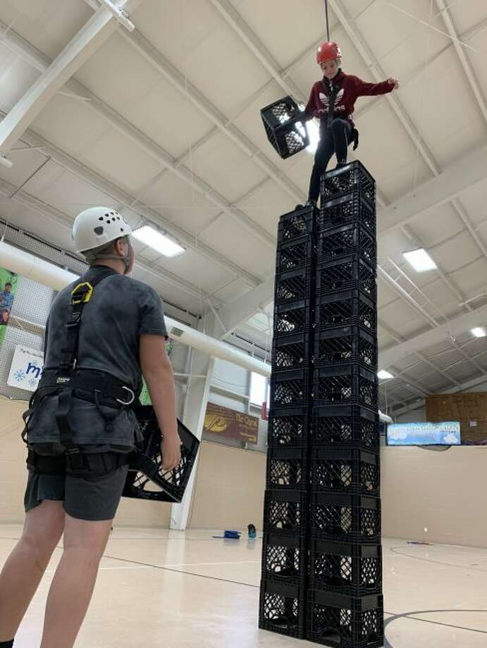 Nate Corey participates in the crate stacking challenge, as he is supported and encouraged by his classmate Adam Domres.