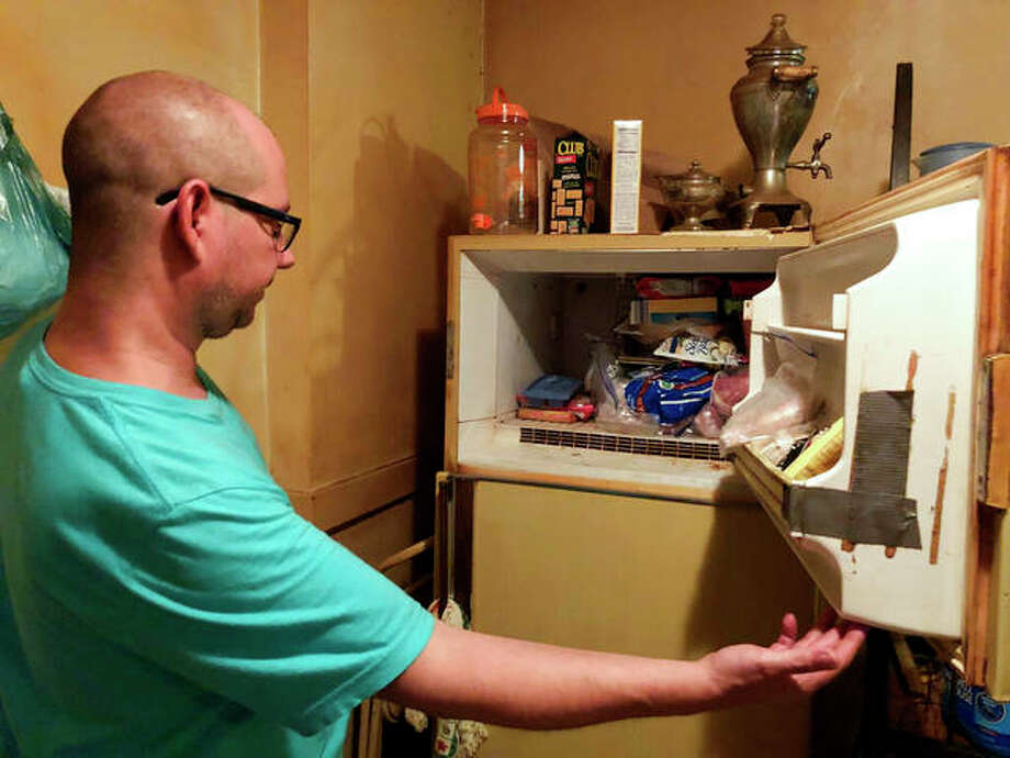 Adam Smith peers into his mother's freezer in St. Louis, where he found the remains of an infant wrapped in a box she kept there for more than 40 years. Police said the death is being investigated as suspicious pending an autopsy. Smith says he was going through his mom's belongings on Sunday after she died July 21 from lung cancer. Photo: Christine Byers | St. Louis Post-Dispatch (AP)
