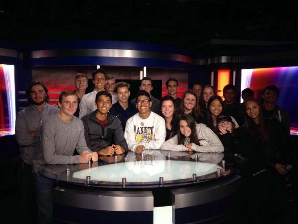 Members of the Manistee High School video production class pose in front of the anchor desk at TV 9 & 10 news station. Students recently toured the station to learn how a newscast is put together.