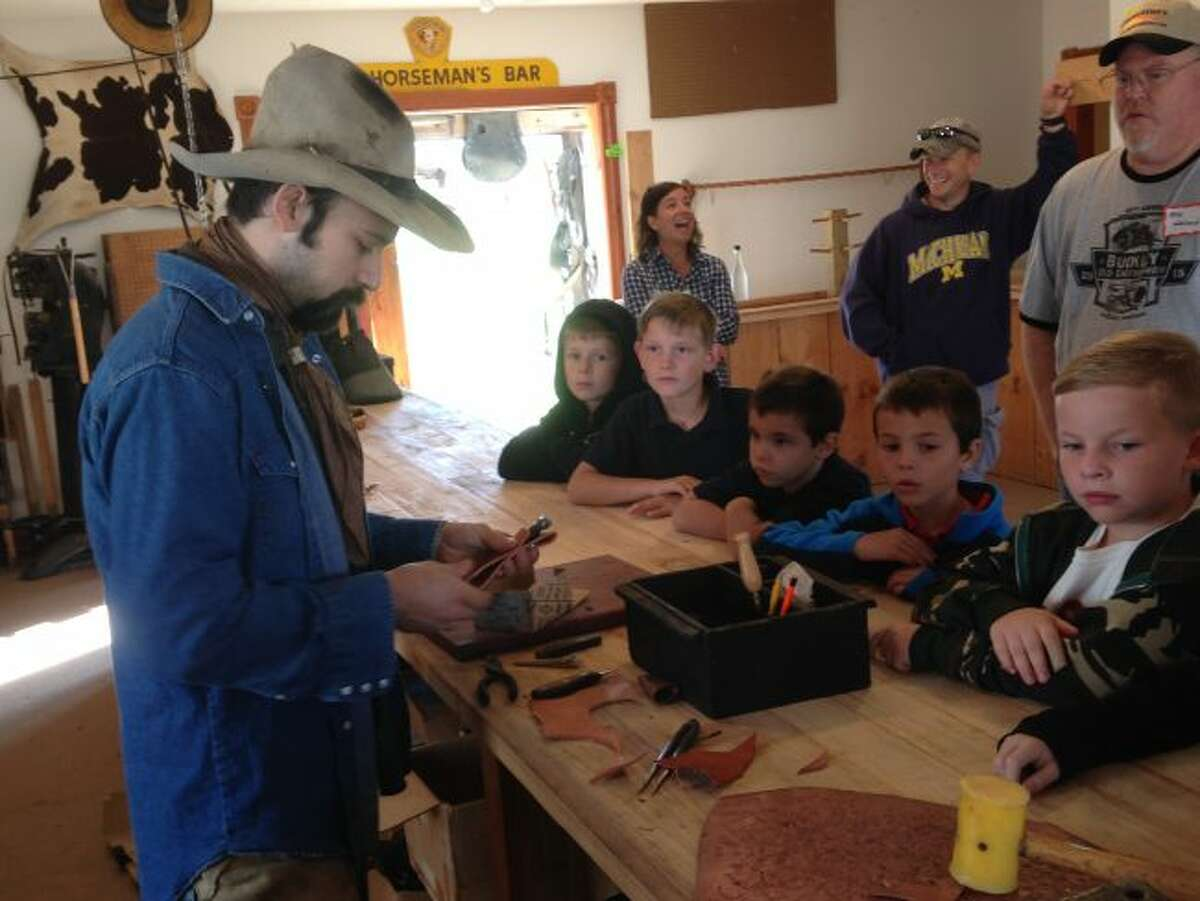Elementary students from Nick Fedder's class at Manistee Catholic Central took a step back in time to take part in the Buckley Old Engine Club Education day recently. By attending the event the students were given the chance to take part in activities like watching how this cow hand made leather pouches for his knives.
