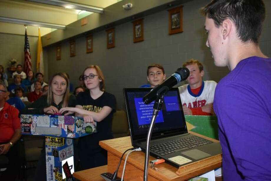 A moderator asks question to two members of different classes in the Jeopardy game that Manistee Catholic Central students participated in Friday as a part of College Application Week. The questions pertained to college related information.