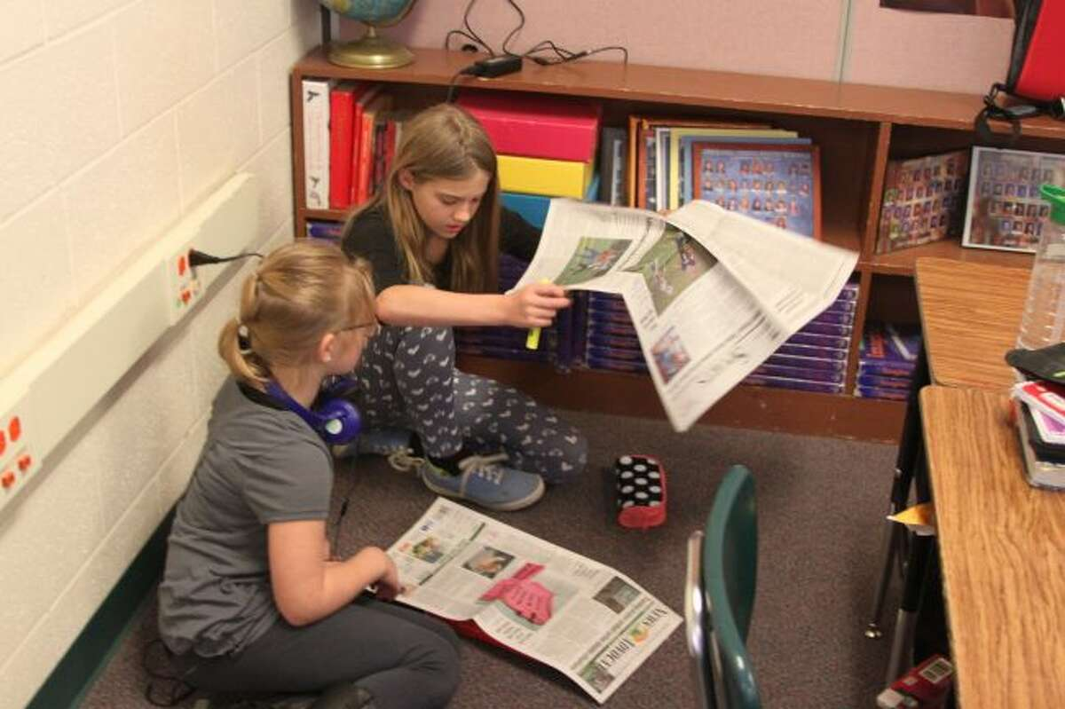 One of the things the students from Tracy Bennett's class in Onekama Consolidated Schools do when the read the Manistee News Advocate is get comfortable. Students have the option of reading a news or sports story to look for assigned tasks that they must find in the paper.