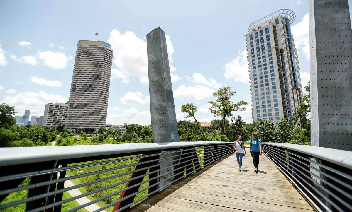 Laura Conely, right, founder of Urban Paths, talks with her client, Chandra Attayi, during their session, as they walk on a pedestrian bridge over Buffalo Bayou.