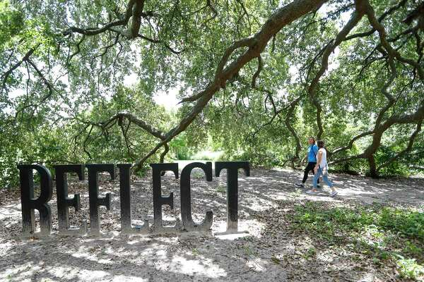 """Laura Conely, left, founder of Urban Paths, talks with her client, Chandra Attayi, walk past a sculpture that reads """"reflect"""" during their session, as they walked the trails along Buffalo Bayou, Monday, July 1, 2019, in Houston. Conely is a nutritionist and life coach, who works one-on-one with clients, while they walk on trails throughout Houston."""