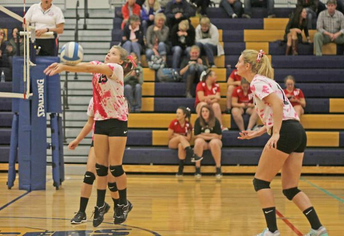 Brian Fogg/News AdvocateOnekama freshman Hanna Hughes bumps the ball over the net while senior McKayla Haske looks on in the Portagers' three-set win over Mason County Eastern.