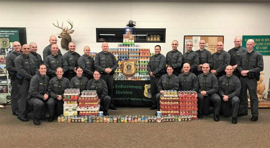 Class members of the Michigan Department of Natural Resources Conservation Officer Recruit School present the food items they raised to support Michigan Harvest Gathering. Recruits raised and donated more than 1,800 items that will help needy families across Michigan through the state's annual food drive.