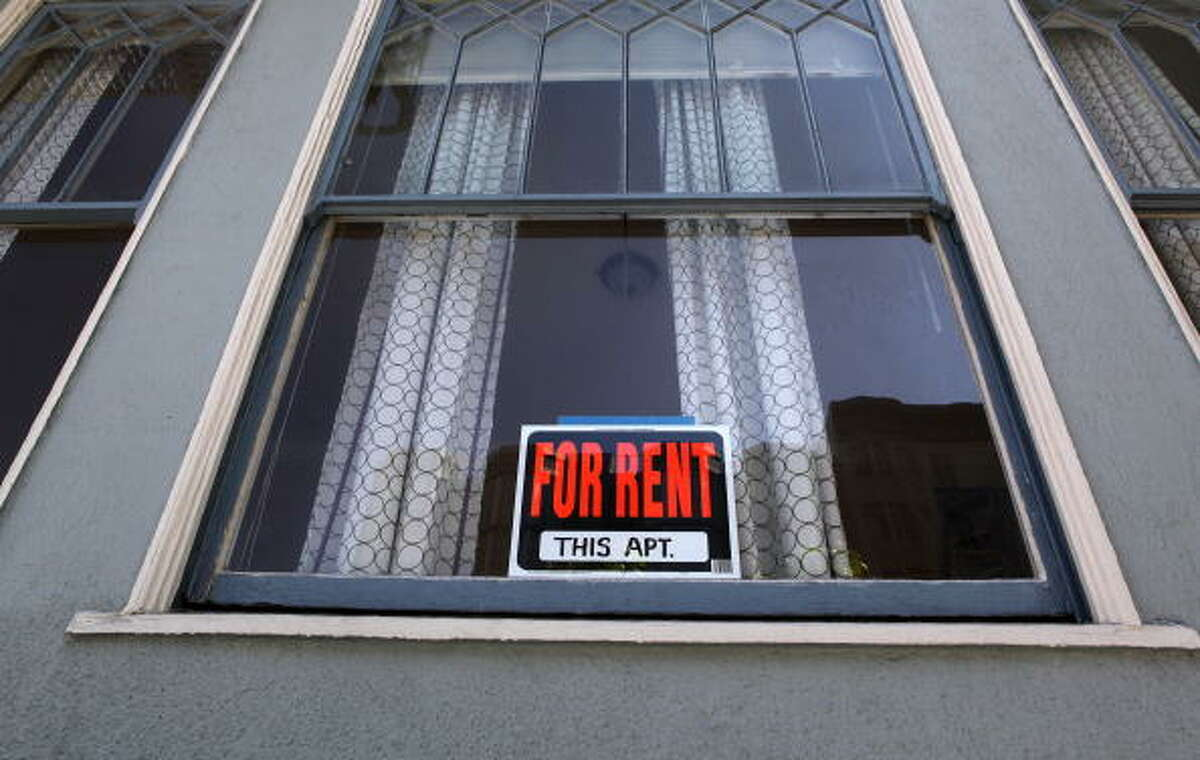 A sign advertising an apartment for rent is displayed in a window.